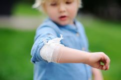 Cute little boy looking on his elbow with applied bandage. Child healthcare and medicine concept. First aid Stock Image