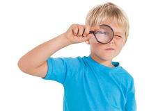 Cute little boy looking through magnifying glass Royalty Free Stock Images