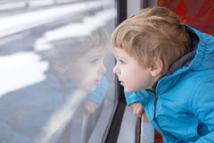 Cute little boy looking out train window. Outside, while it moving. travel Royalty Free Stock Photo