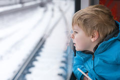 Cute little boy looking out train window. Beautiful toddler boy looking out train window outside, while it moving. travel Stock Images