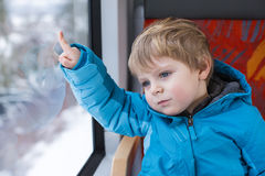 Cute little boy looking out train window. Outside, while it moving. travel Royalty Free Stock Photos