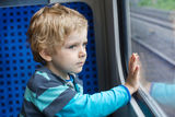 Cute little boy looking out train window. Adorable toddler boy looking out train window outside, while it moving. travel Stock Photo