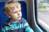 Cute little boy looking out train window. Beautiful toddler boy looking out train window outside, while it moving. travel Royalty Free Stock Photo