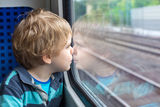 Cute little boy looking out train window Stock Photos