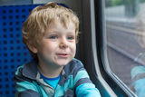 Cute little boy looking out train window. Beautiful toddler boy looking out train window outside, while it moving. travel Stock Photography