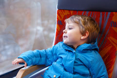 Cute little boy looking out train window. Lovely toddler boy looking out train window outside, while it moving Stock Photography