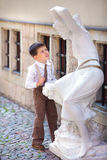 Cute little boy looking at white statue Royalty Free Stock Images