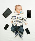 Cute little boy lying on bed with digital tablets and smartphone Stock Photography