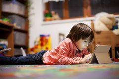 Cute little boy, lying on the floor in kids room, playing on tab Stock Photography