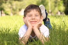 Cute little boy lying on green grass Stock Images