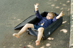 Cute little boy lying in a suitcase Stock Photos