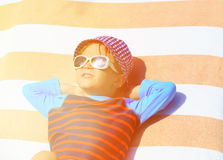 Cute little boy lying on towel at summer beach Royalty Free Stock Image