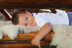 Cute  little boy lying on wooden bench. With soft fluffy blanket summer evening terrace. Children smiling. concept of childhood Royalty Free Stock Photography