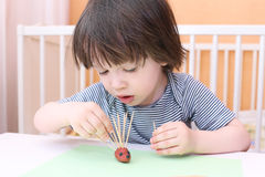 Cute little boy made toothpick spines by playdough hedgehog Stock Photography