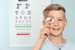 Cute little boy with magnifier in office. Cute little boy with magnifier in ophthalmologist office royalty free stock photo