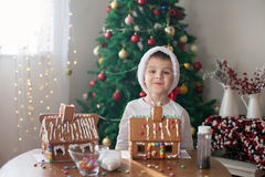 Cute little boy, making gingerbread cookies house for Christmas Royalty Free Stock Photos