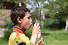 Cute little boy making soap bubbles Stock Photo