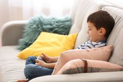 Cute little boy with mobile phone on sofa. At home Royalty Free Stock Photos