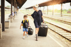 Cute little boy and mother on a railway station. Cute little boy and young mother with suitcases on a railway station Royalty Free Stock Photo