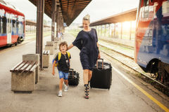 Cute little boy and mother on a railway station. Cute little boy and young mother with suitcases on a railway station Stock Photos
