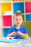 Cute little boy moulds from plasticine on table Stock Photos