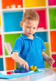 Cute little boy moulds from plasticine on table Stock Image