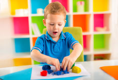 Cute little boy moulds from plasticine on table Royalty Free Stock Photo
