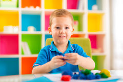 Cute little boy moulds from plasticine on table Royalty Free Stock Photos