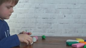Cute little boy moulds from plasticine on table. 4k video stock video footage