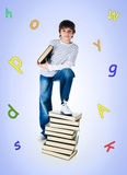 Cute little boy near the stack of big books Royalty Free Stock Photos
