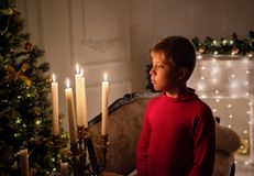 Cute little boy on a New Year`s background looking at candles royalty free stock photo