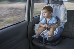 Cute little boy observing the countryside from his car safety se. At. He is distracted by the landscape Stock Photo