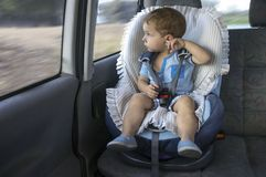 Cute little boy observing the countryside from his car safety se. At. He is distracted by the landscape Stock Photos