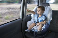 Cute little boy observing the countryside from his car safety se. At. He is pointing something Stock Images