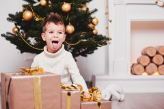 Cute little boy open his mouth and showing tongue near a lot of gifts with golden ribbons and bows. Guy in a knitted sweater and s. Tylish hair on the background stock photo