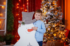 Cute Little Boy opening Gift box under Christmas Tree in red house interior Royalty Free Stock Image