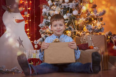 Cute Little Boy opening Gift box under Christmas Tree in red house interior Stock Photos