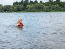 Cute little boy in orange life vest swimming in the river. Little boy in orange life vest swimming in the river royalty free stock photo