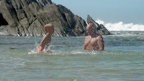 Cute boy splashes water on daddy playing in calm sea bay