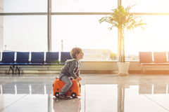 Cute little boy with orange suitcase at airport royalty free stock photo