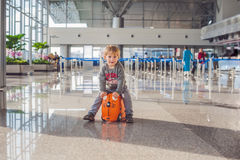 Cute little boy with orange suitcase at airport Royalty Free Stock Photography