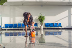 Cute little boy with orange suitcase at airport Stock Photo