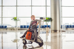 Cute little boy with orange suitcase at airport. The boy on the trolley and the airport Stock Image
