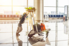 Cute little boy with orange suitcase at airport. The boy on the trolley and the airport Stock Images