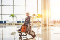 Cute little boy with orange suitcase at airport. The boy on the trolley and the airport Royalty Free Stock Image