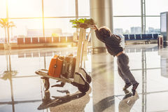 Cute little boy with orange suitcase at airport. The boy on the trolley and the airport Stock Photo