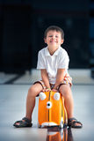 Cute little boy with orange suitcase at airport Stock Photography