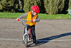 Cute little boy out riding his bike Stock Photo