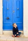 Cute little boy outdoors against blue door Stock Photo