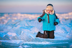 Cute little boy outdoors playing on winter beach. On beautiful winter day Royalty Free Stock Photos